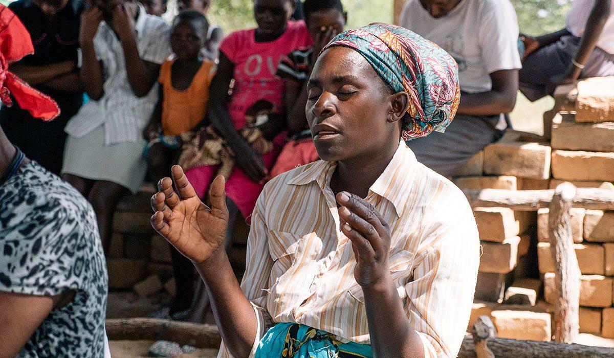 Woman praying in Zimbabwe