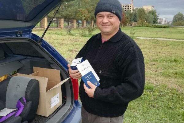 Smirnov showing the gospel literature he carries in the trunk of his Taxi.